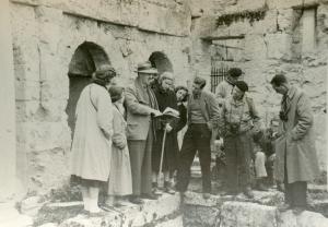 John Caskey explaining the plan of the Spring of Pirene in Corinth; Left to Right: Nancy Ashby, Barbara Hughes, John Caskey, Pam Wiegand, Christine Mitchell, Ruth Allen, Dough Feauer, Bob Held, Mr. Pritchett, Norm Doenges (seated), Mr. Vanderpool; Corinth, 26 Nov. 1951 (photo: Matthew Wiencke)